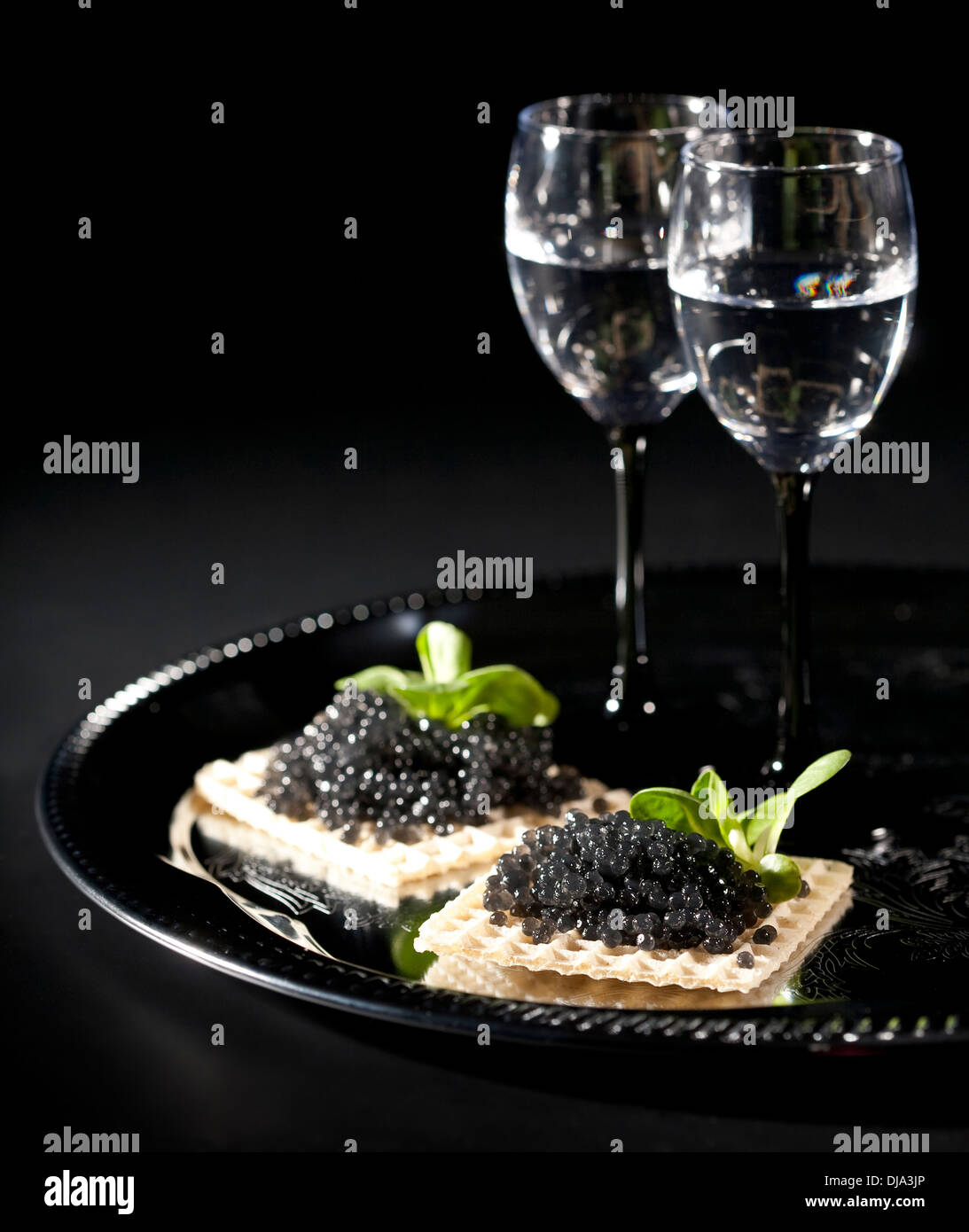 Vodka and black caviar on black background - Stock Image