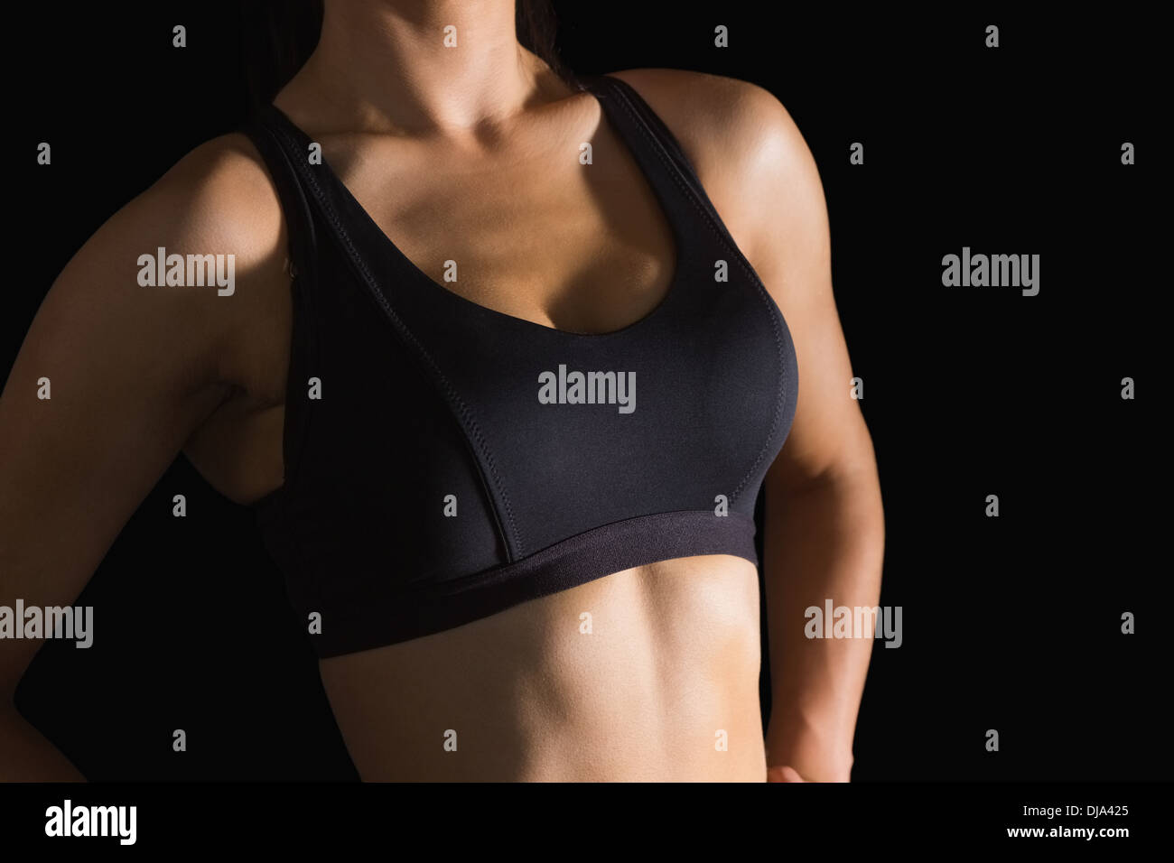 Mid section of slender woman wearing sports bra - Stock Image