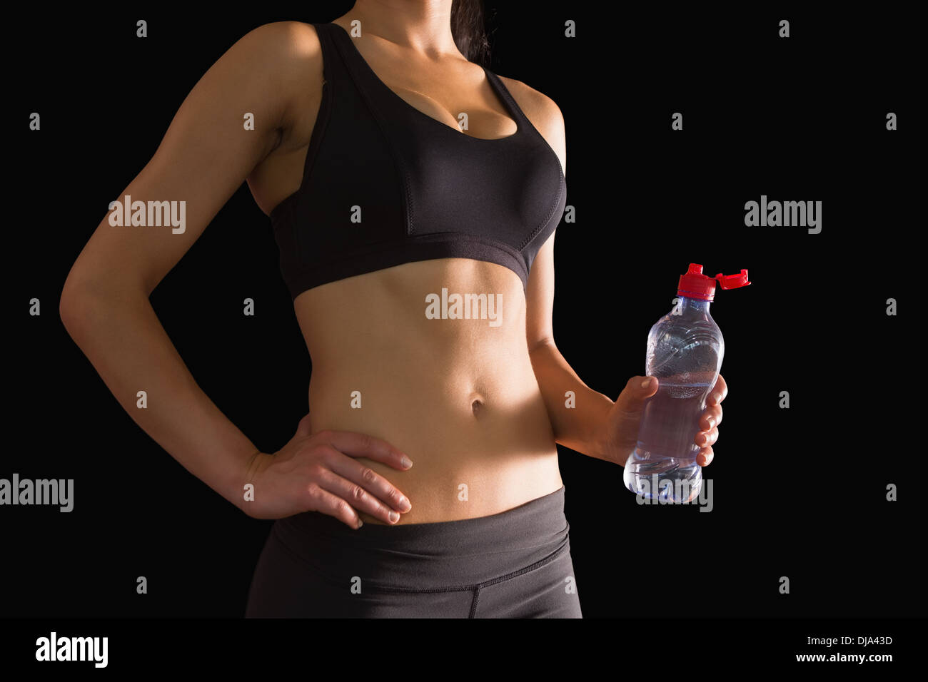 Mid section of slim woman holding a bottle of water - Stock Image