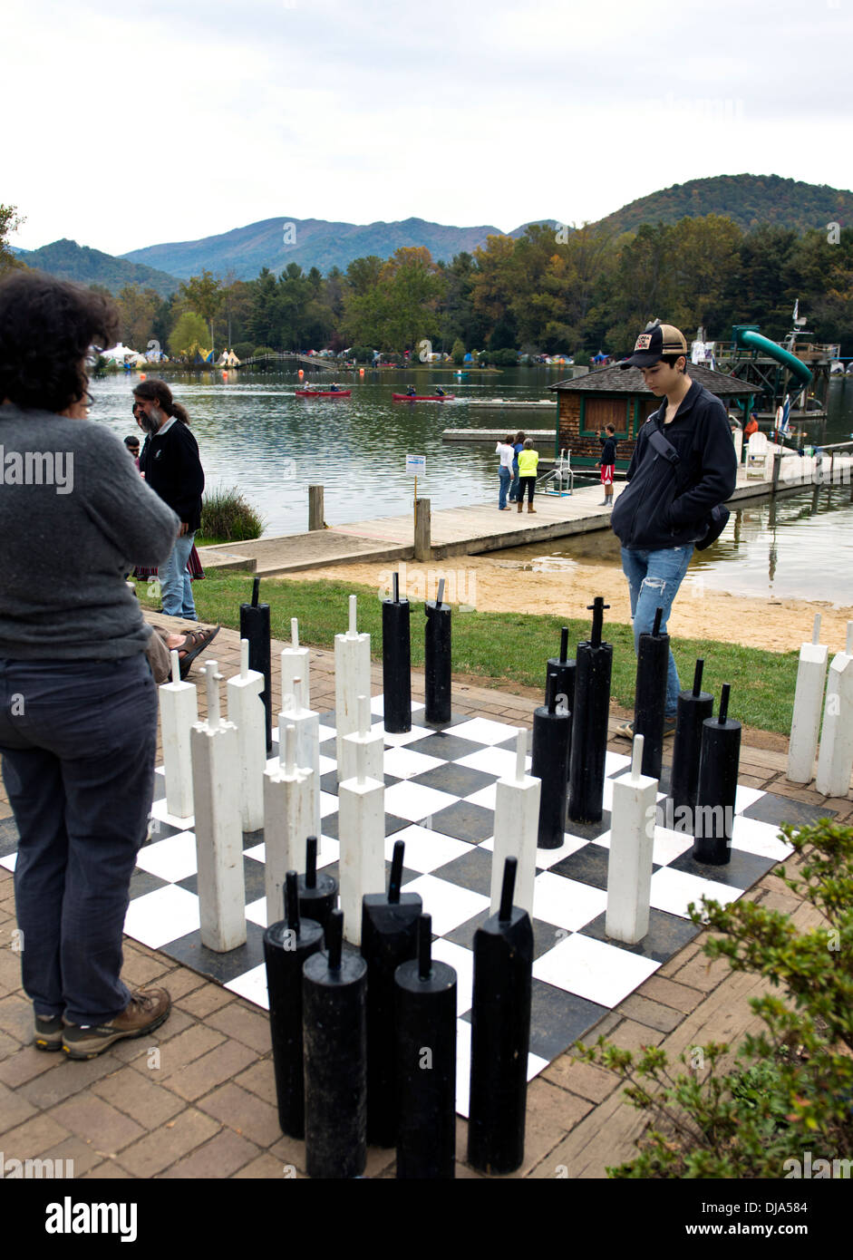 People playing chess on an oversize game board at the Leaf Festival (Lake Eden Arts Festival) Black Mountain, North Carolina - Stock Image