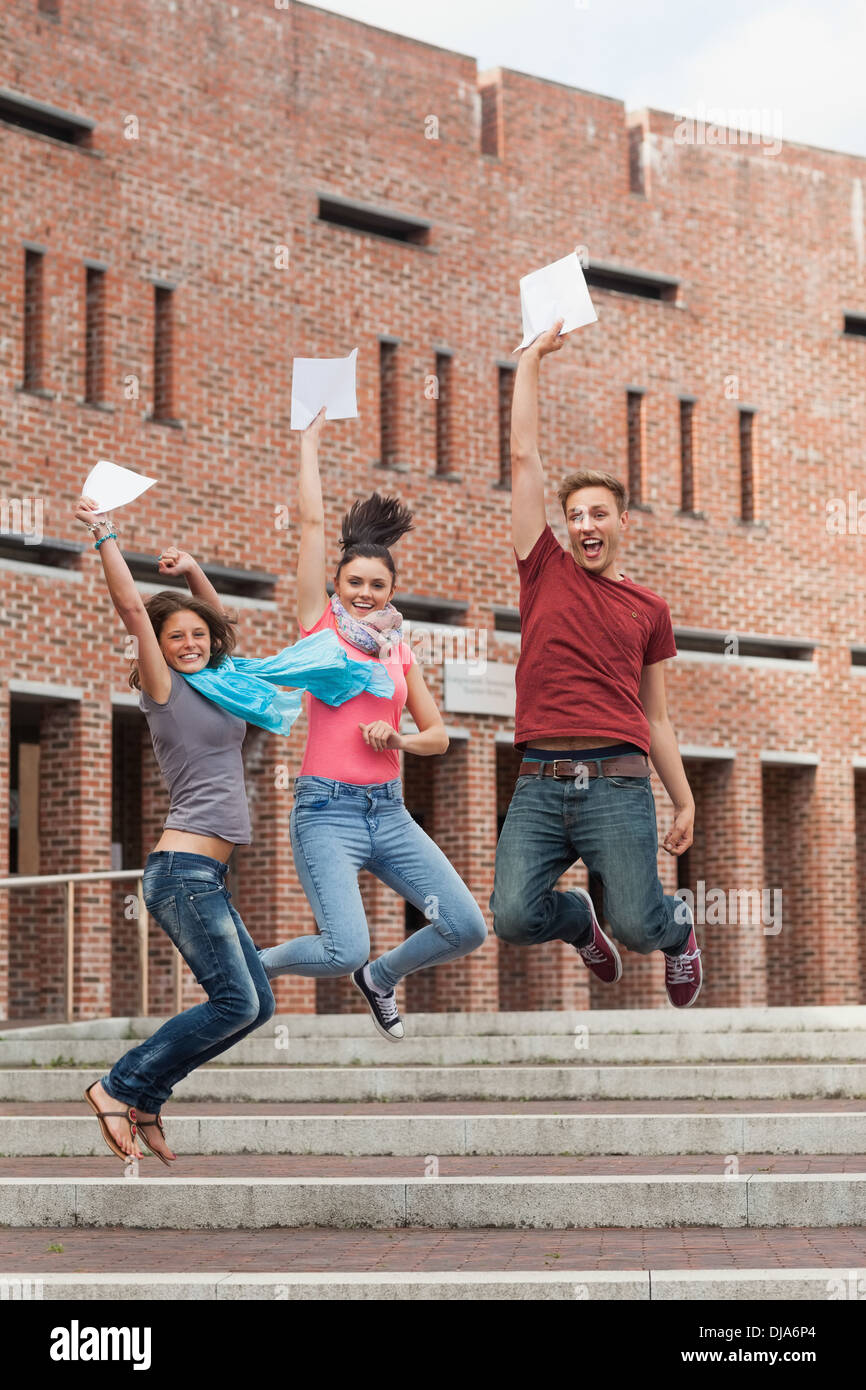 Happy students jumping in the air holding exam - Stock Image