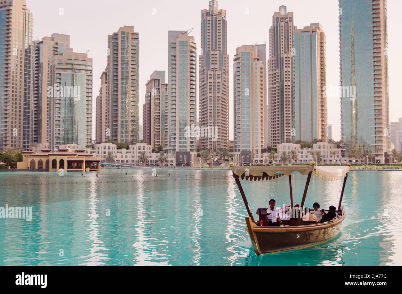 Tourists riding an abra on the waters of the man-made Burj Khalifa Lake. Dubai, United Arab Emirates. - Stock Image
