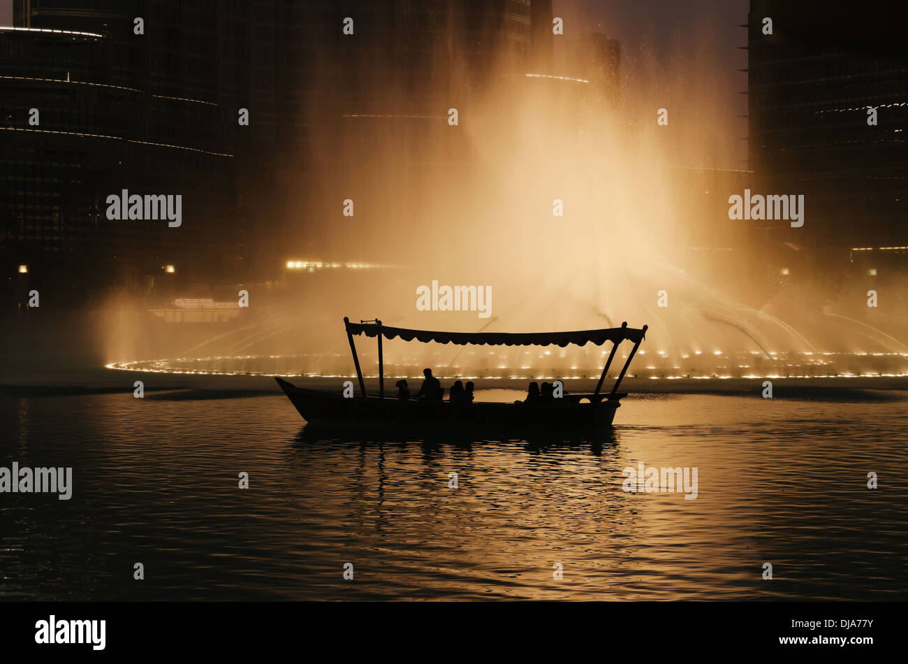 Spectators riding a traditional abra to enjoy the musical show at The Dubai Fountain. Dubai, United Arab Emirates. - Stock Image