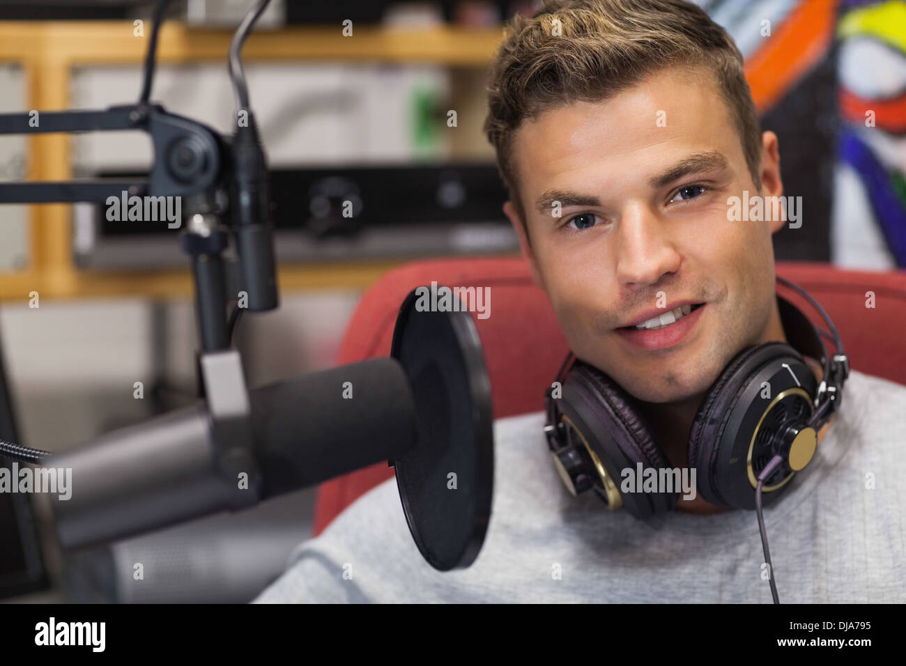 Handsome smiling singer recording a song - Stock Image