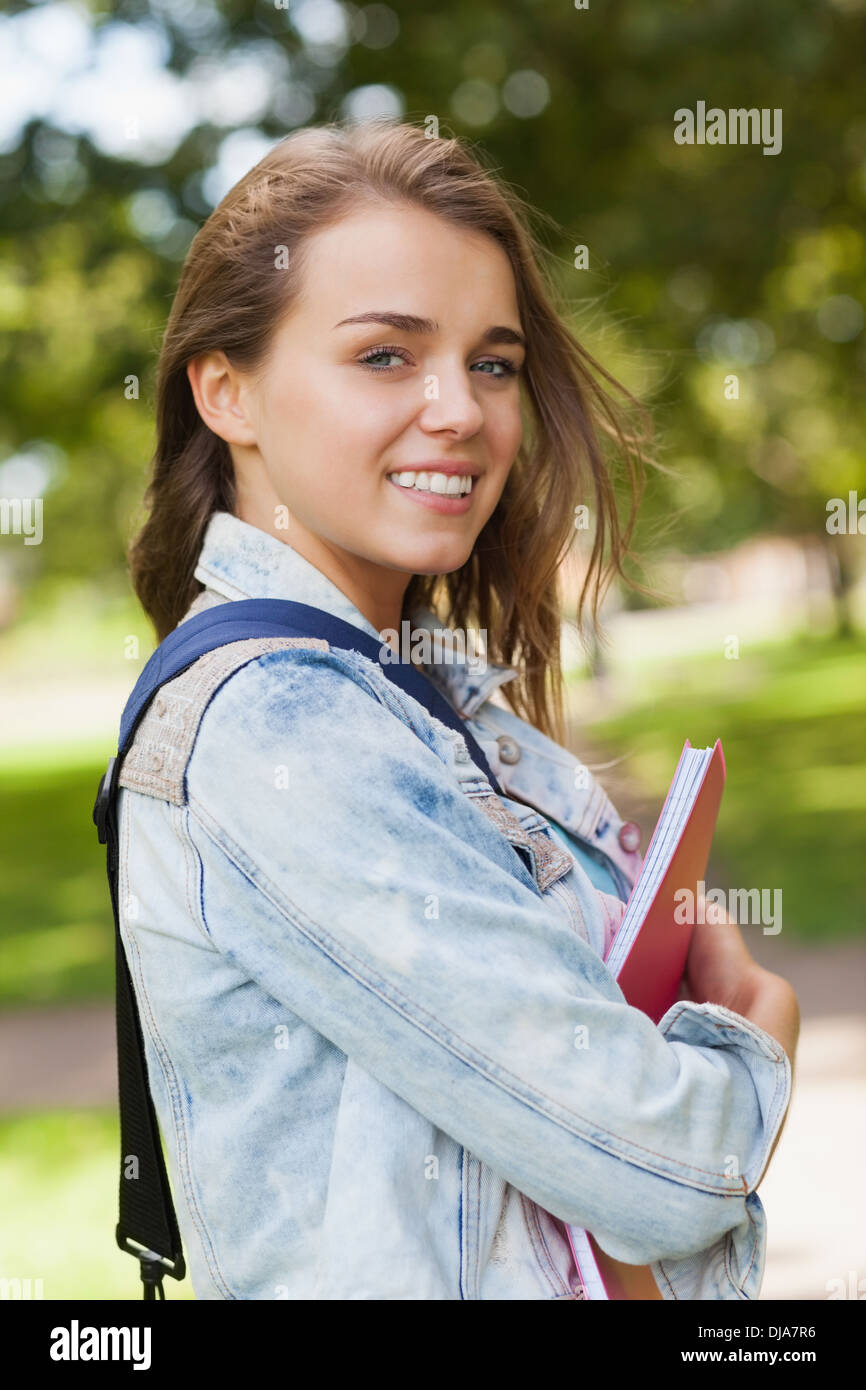 Pretty gleeful student holding folder and notebook - Stock Image