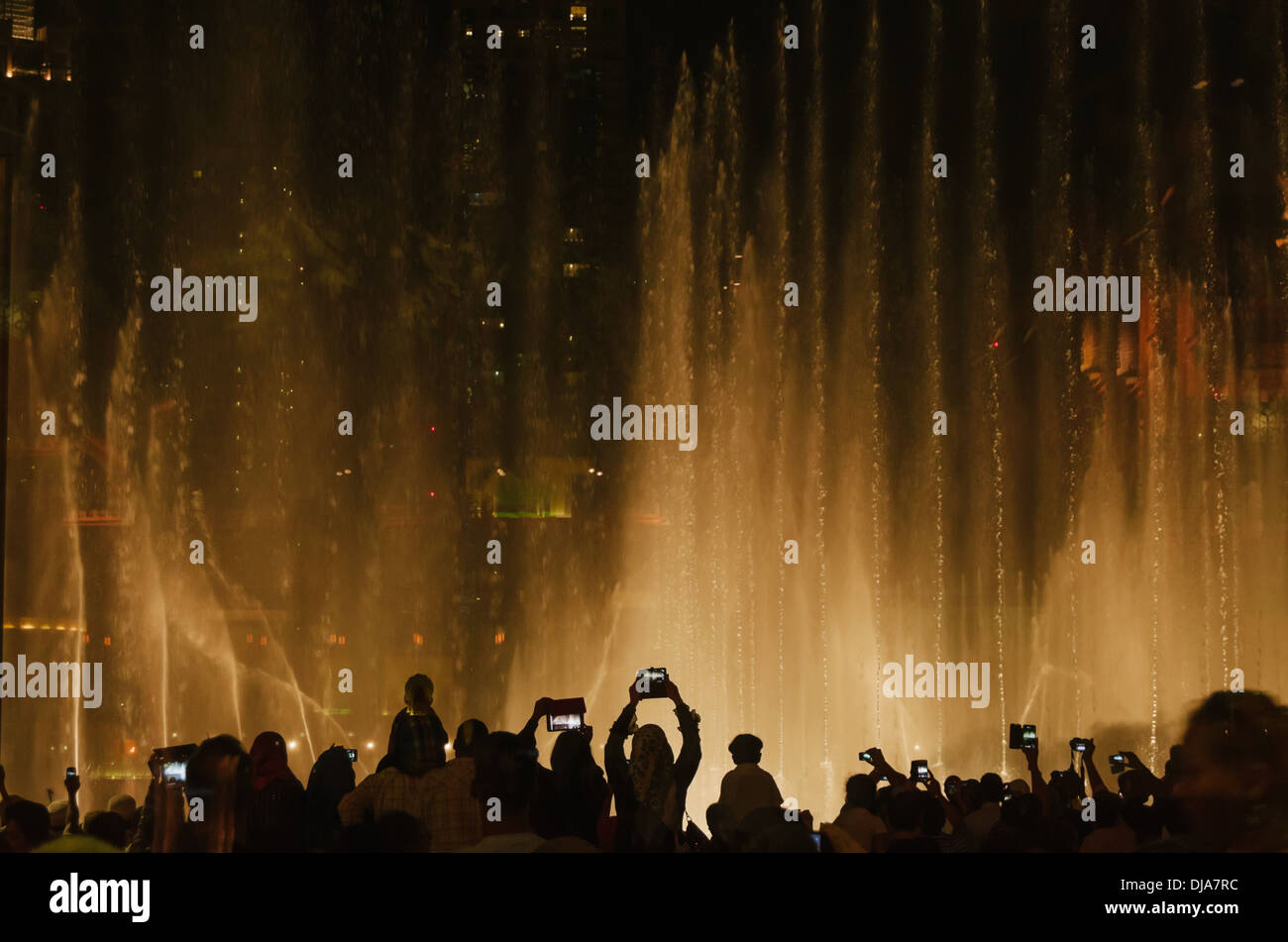Spectators taking pictures with cell phones and tablets during the musical show at The Dubai Fountain. Dubai, UAE. - Stock Image
