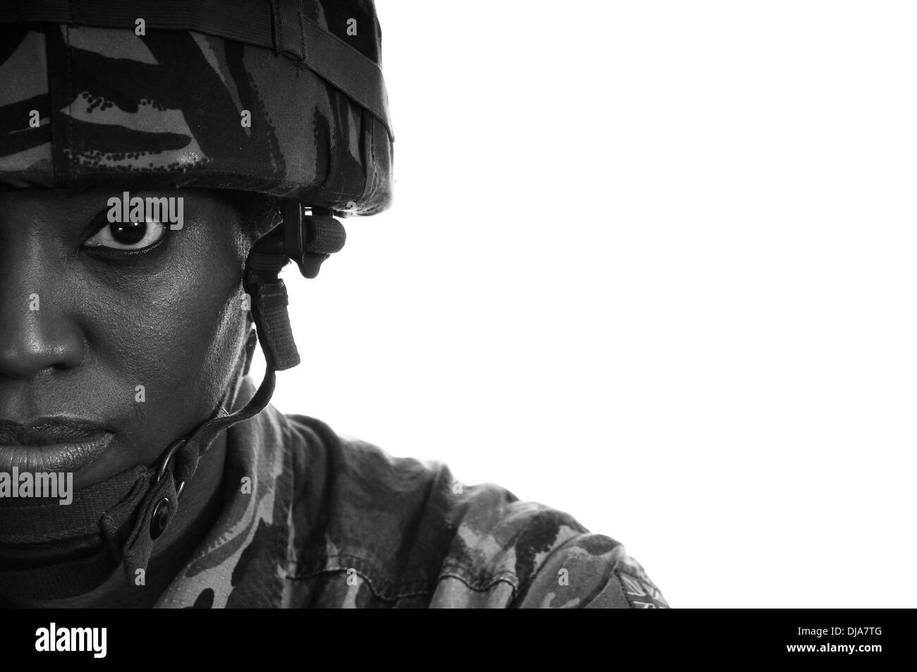 Half face portrait of a black female British soldier against a white background. - Stock Image