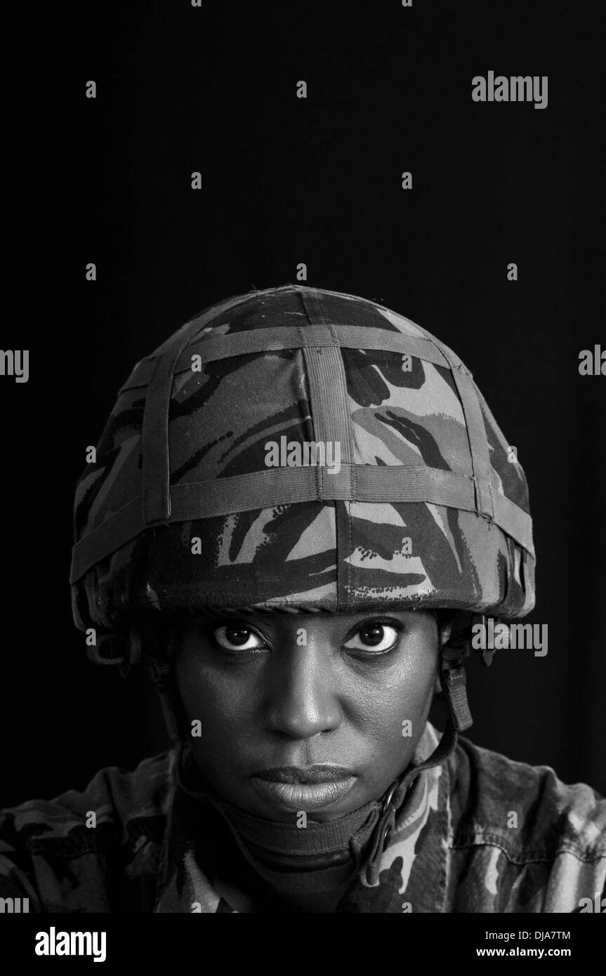 Black & white portrait of black female British solder against a black background. - Stock Image