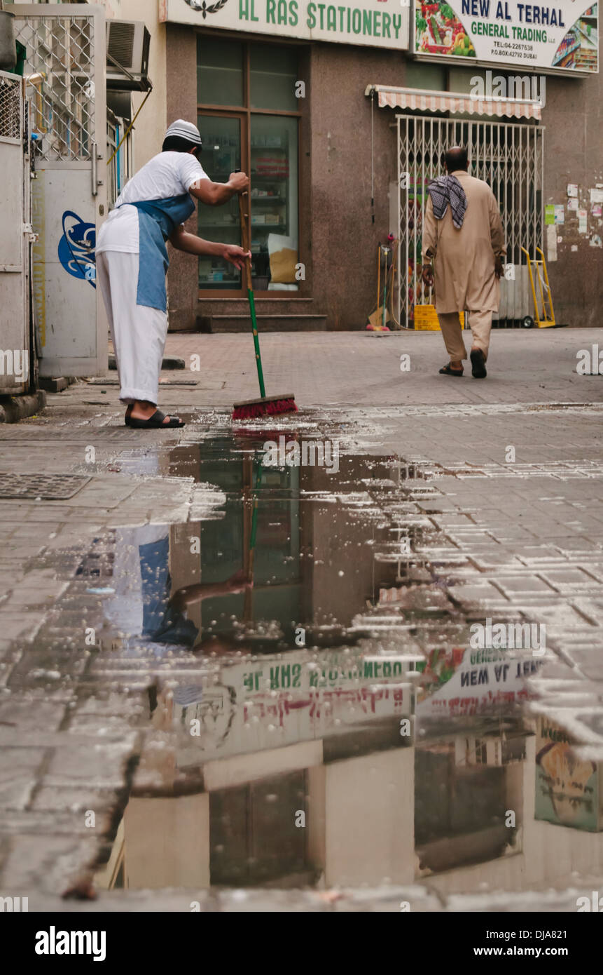 A clerk sweeps the wet pavement outside his store in the streets of Deira. Dubai, United Arab Emirates. - Stock Image