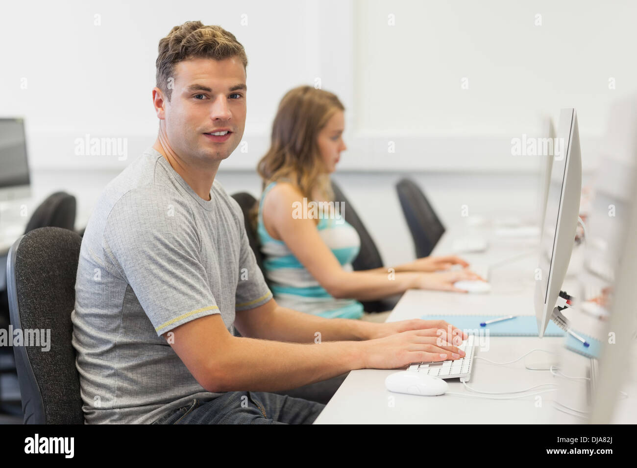 Two happy students working on computer individually - Stock Image