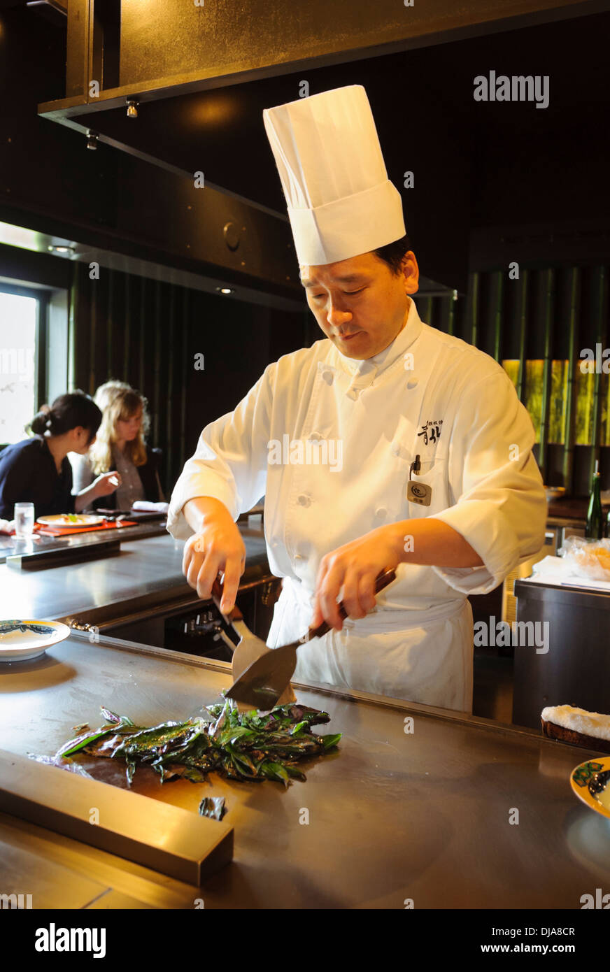 Japanese chef at work in a restaurant, chopping and cooking green vegetables on a hot plate in the open kitchen. - Stock Image