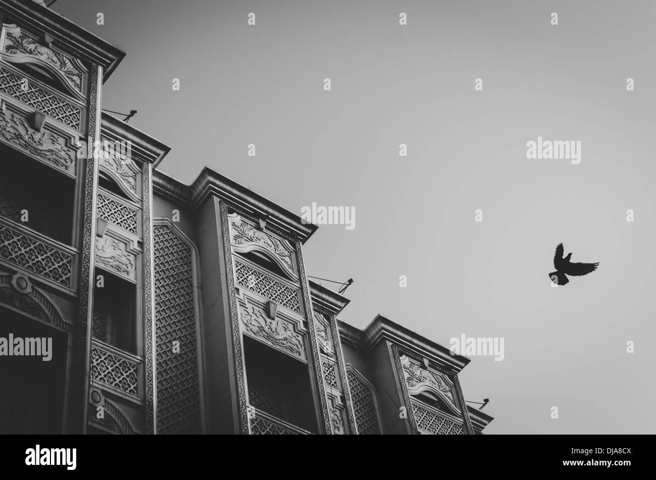 A pigeon flies in front of an apartment building with arabesque motifs in Deira. Dubai, United Arab Emirates. - Stock Image