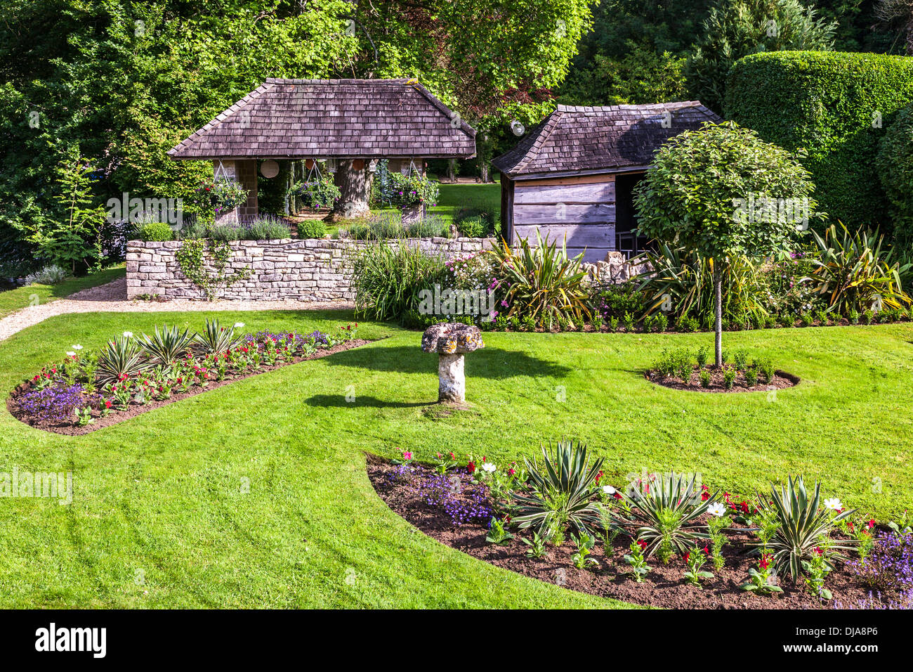 The pretty landscaped garden of the Swan Hotel in the Cotswold village of Bibury in the Coln Valley. - Stock Image