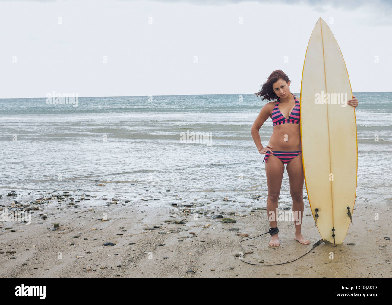 Full length of a bikini woman holding surfboard at beach - Stock Image
