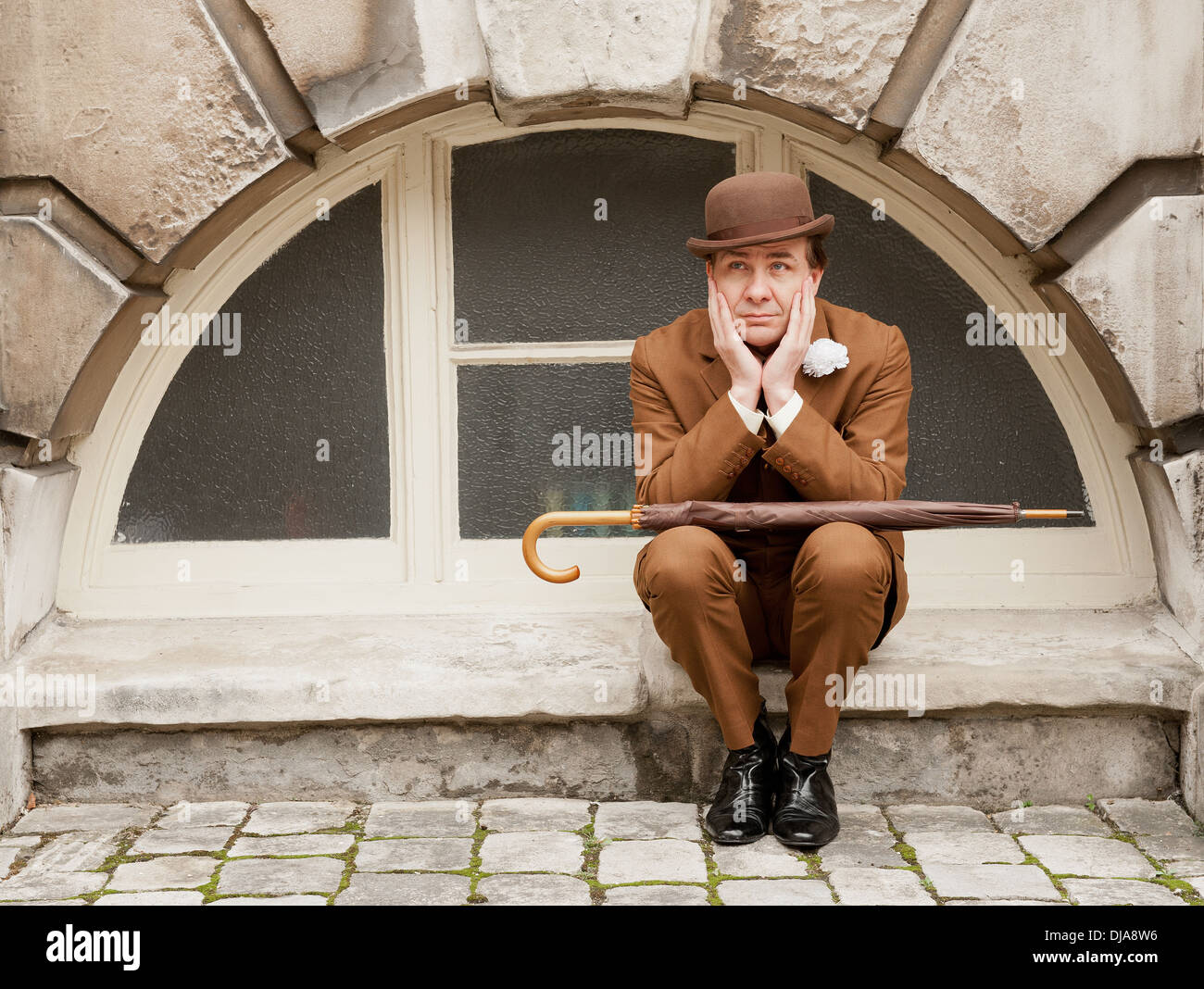 Dapper city gent in a brown suit and matching bowler hat sitting by an arched window with his head in his hands. - Stock Image