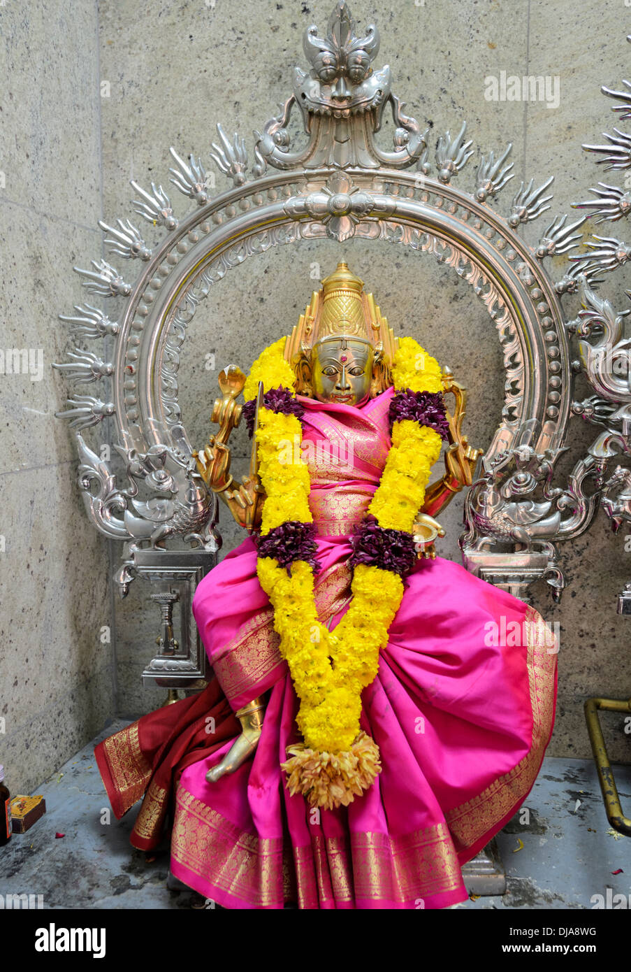 Statue of a four-armed Hindu deity, adorned with a colourful garland of yellow flowers and a pink dress. - Stock Image