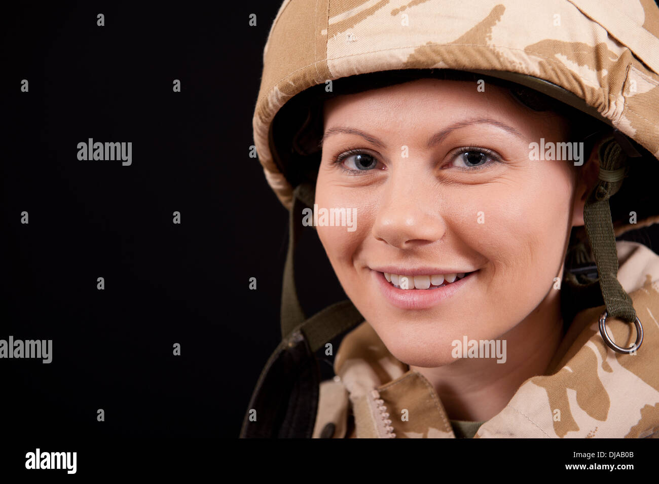 Smiling young female soldier wearing British Military uniform, against a black background. - Stock Image