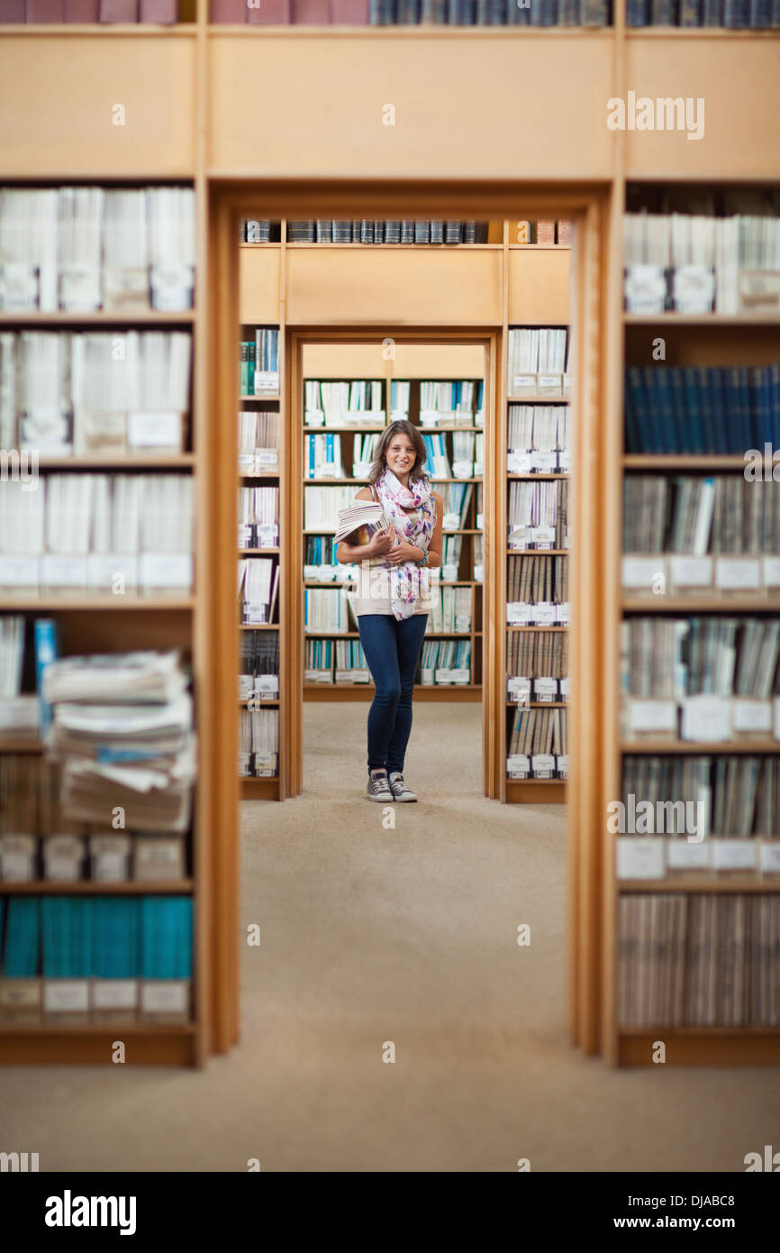 Full lenght of a female student standing in the library - Stock Image
