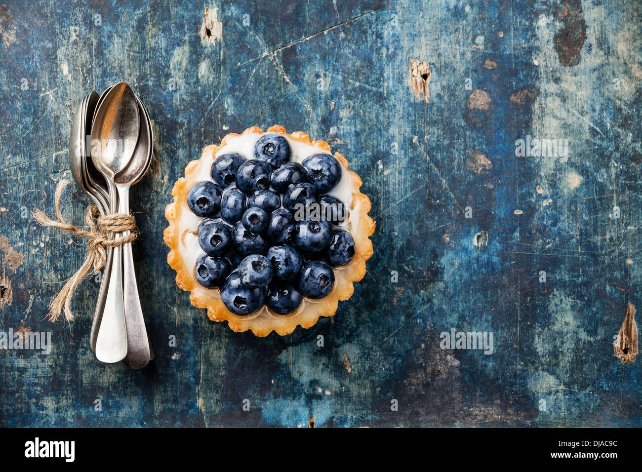 Blueberry tart and Bunch of teaspoons on blue wooden background - Stock Image