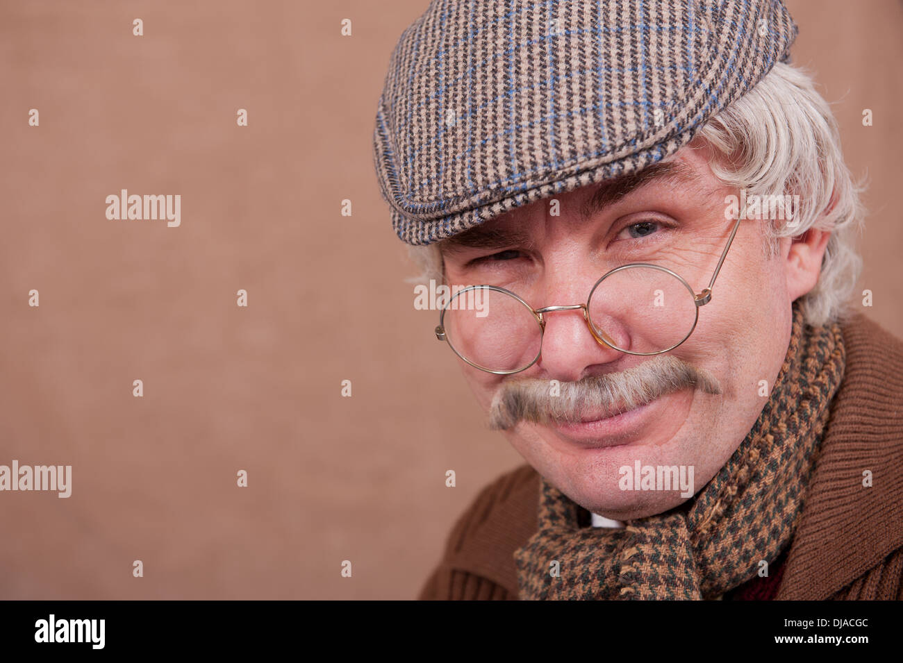 Smiling grey haired old man wearing flat cap,glasses and comfy scarf, against a brown background. - Stock Image