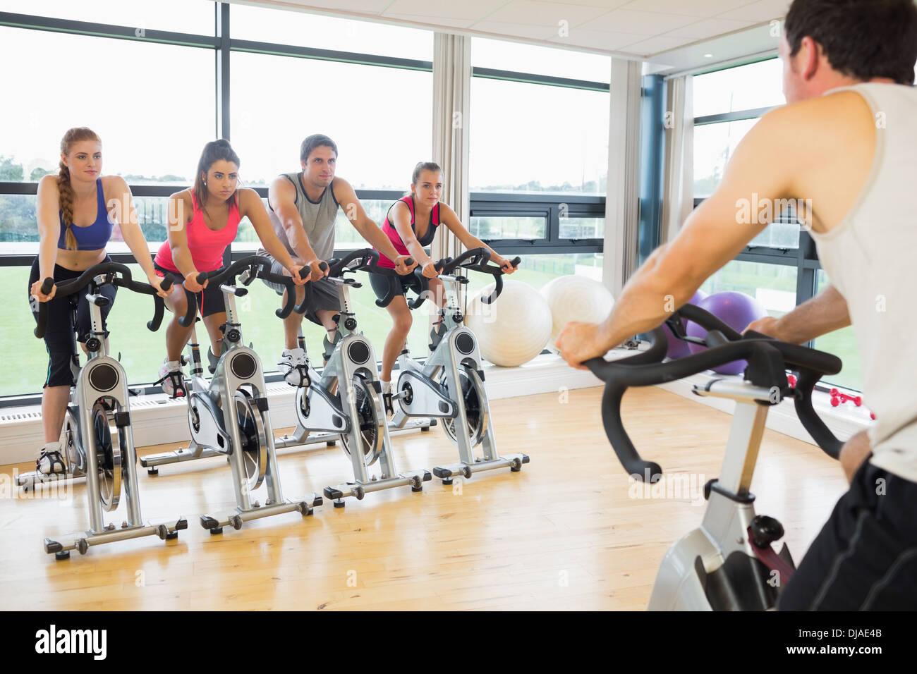 Man teaching spinning class to four people - Stock Image