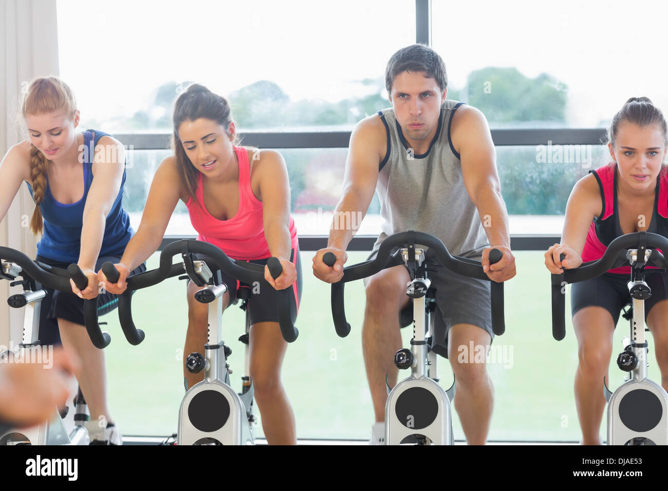 Determined people working out at spinning class - Stock Image