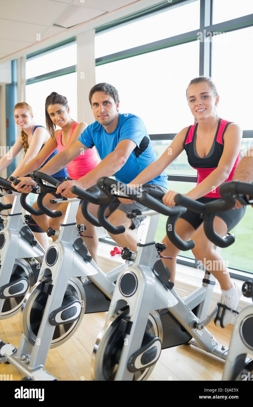Four people working out at spinning class - Stock Image