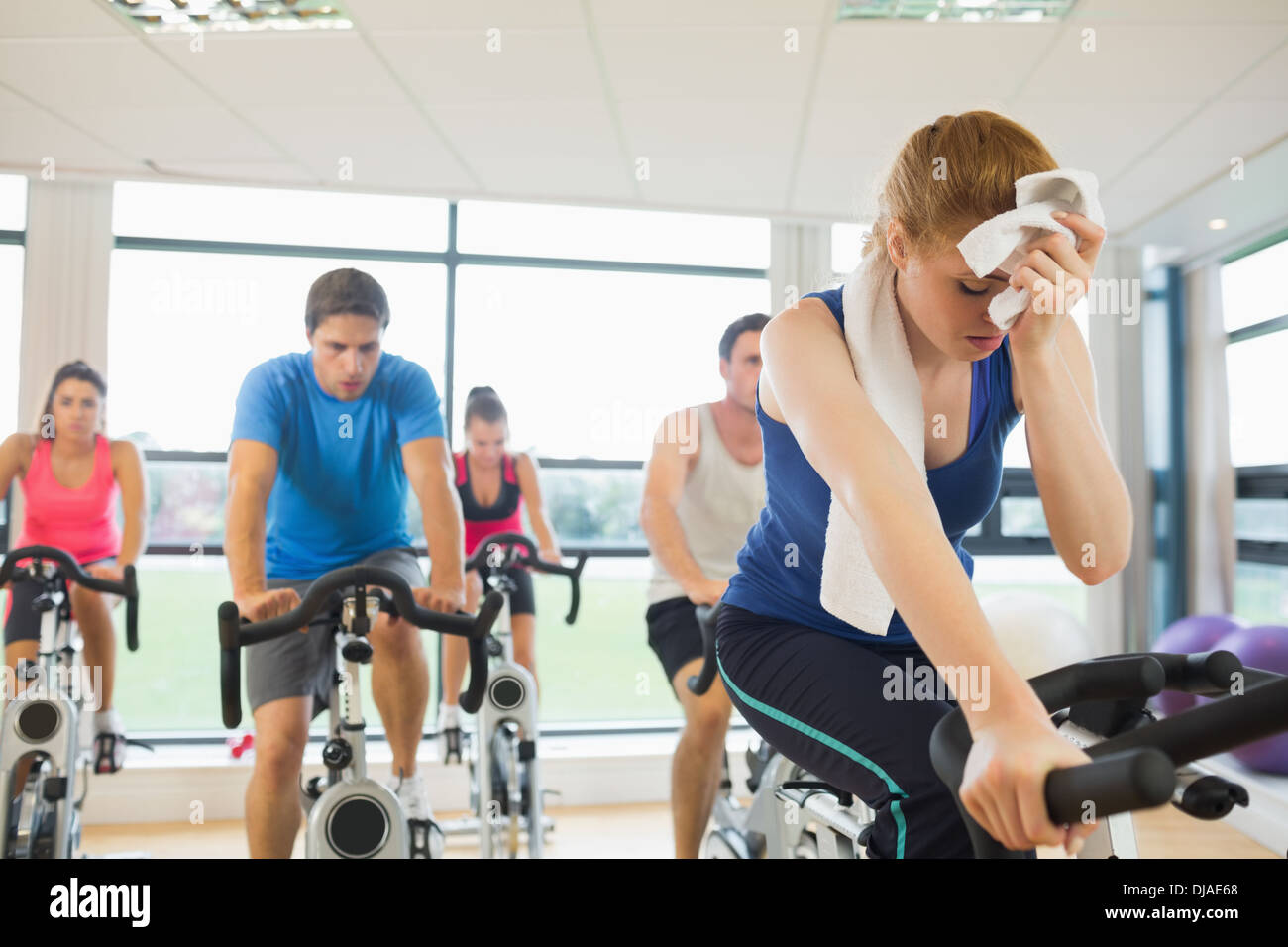 Tired people working out at spinning class - Stock Image