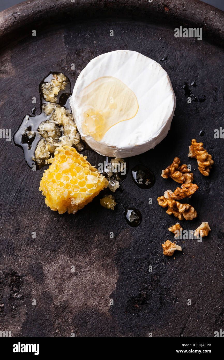 Cheese with honey and nuts on black textured background - Stock Image