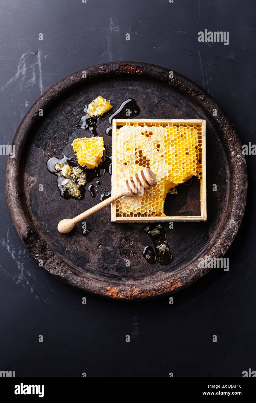 Honeycomb with wooden honey dipper on black textured background - Stock Image