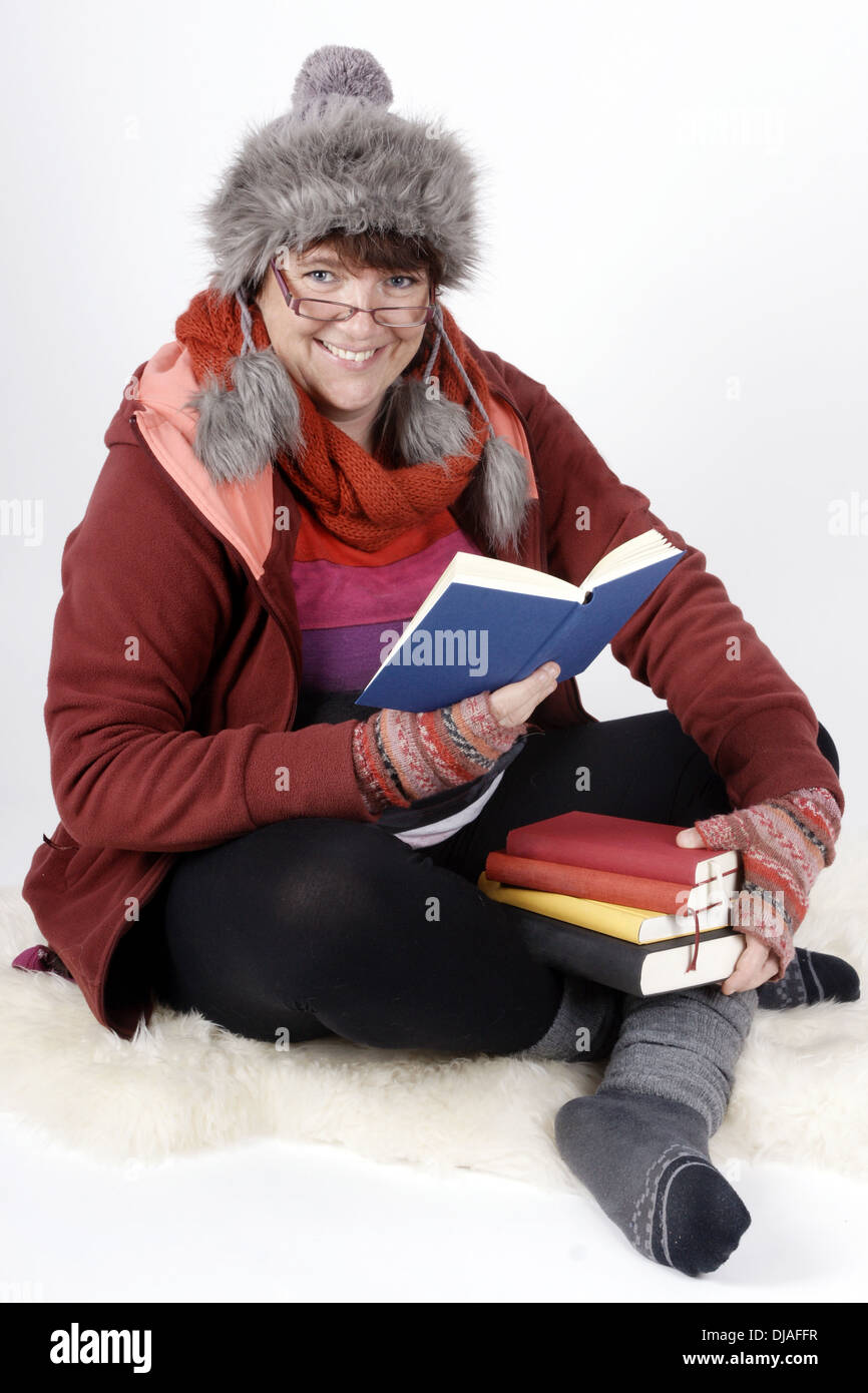 Woman in winterclothes holding a stack of books and reading aloud - Stock Image