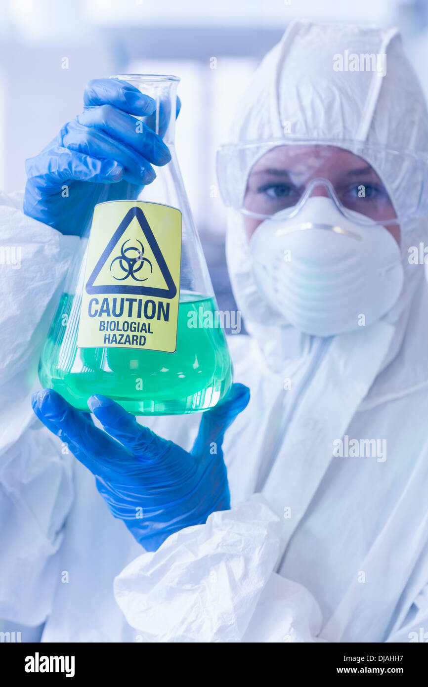 Scientist in protective suit with hazardous chemical in flask - Stock Image