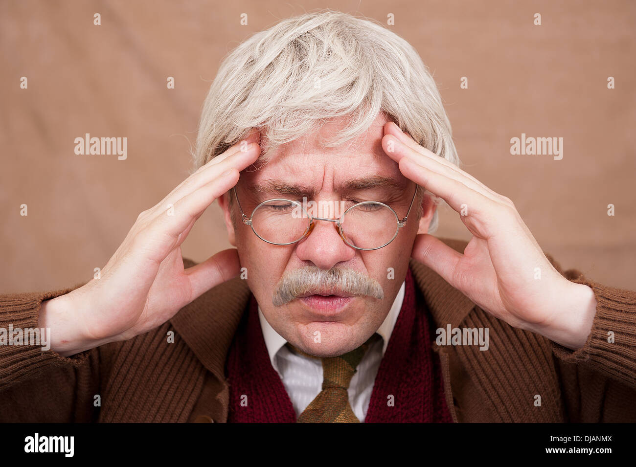 Grey haired old man with his eyes closed and hands to head suffering from a headache. - Stock Image