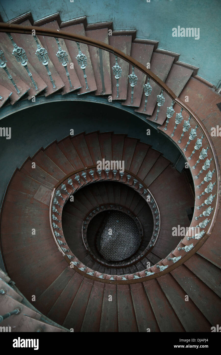 Wooden spiral stairs in tenement house - Stock Image