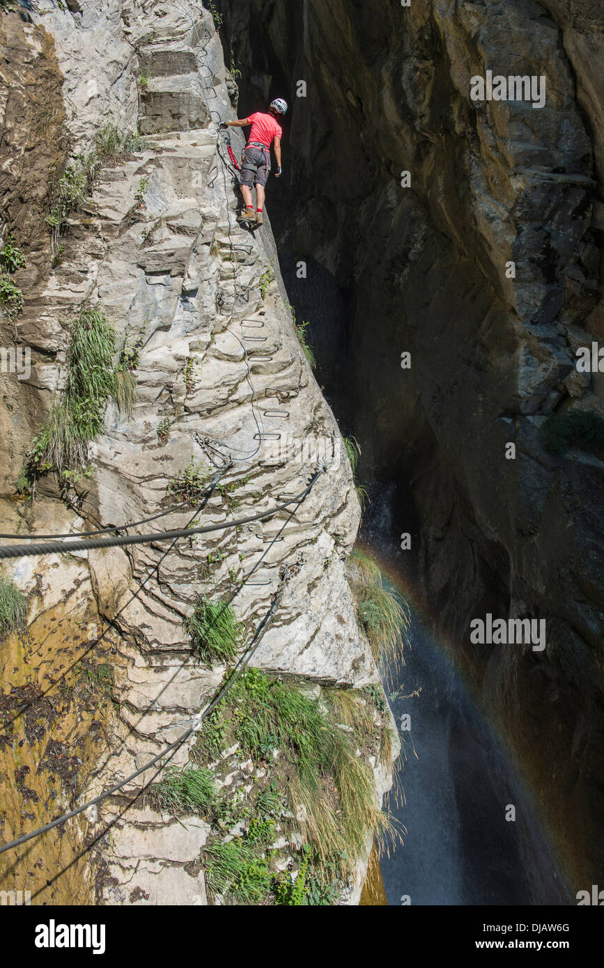 Female climber on the fixed rope route 'Via Farinetta', gorge with waterfall, Leytron, Martigny, Canton of Valais, Switzerland - Stock Image