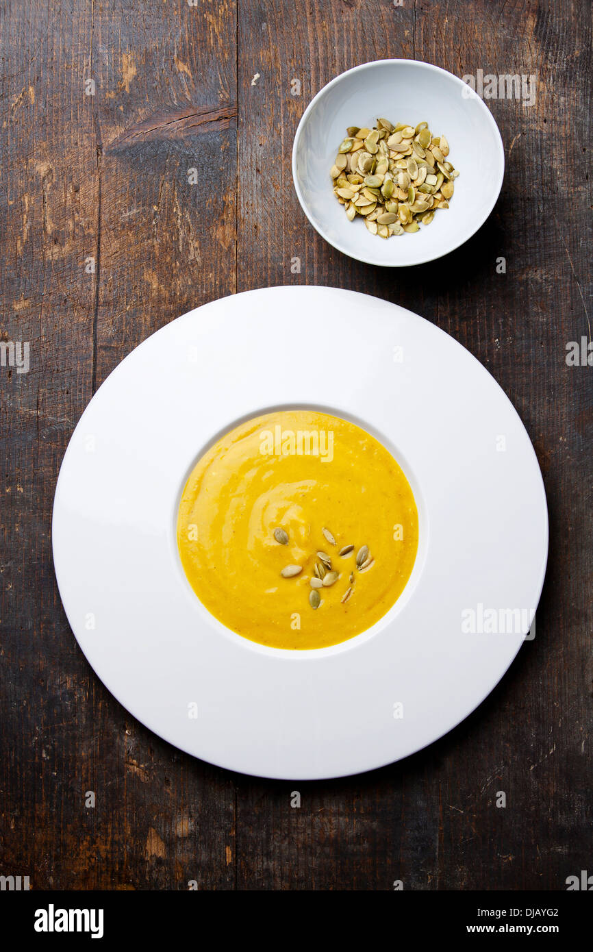 Pumpkin soup with pumpkin Seeds on wooden background Stock Photo