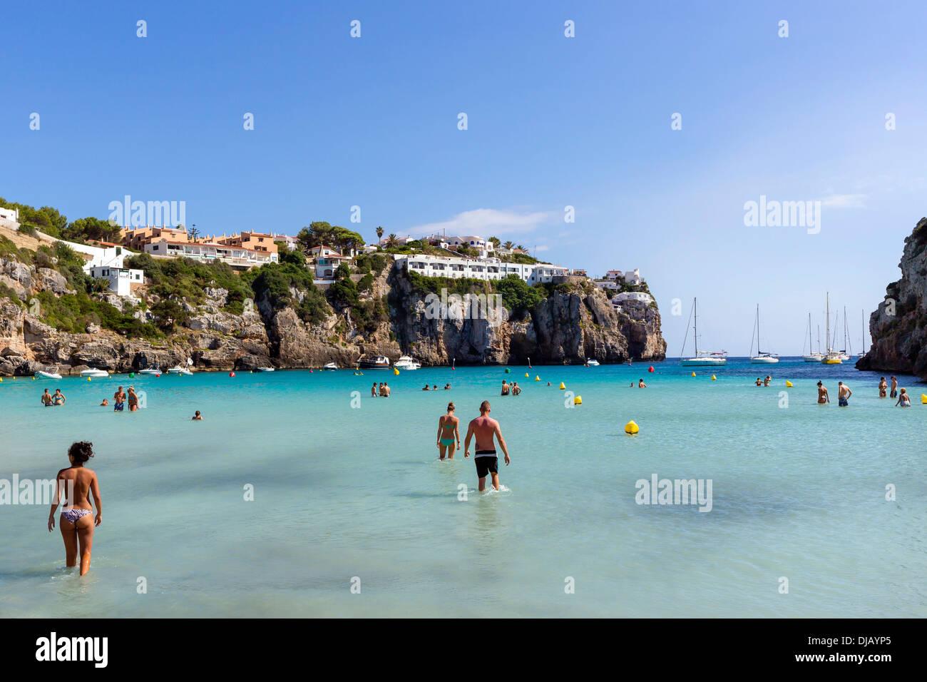 Tourists in the shallow sea, Cala en Porter, Minorca, Balearic Islands, Spain - Stock Image