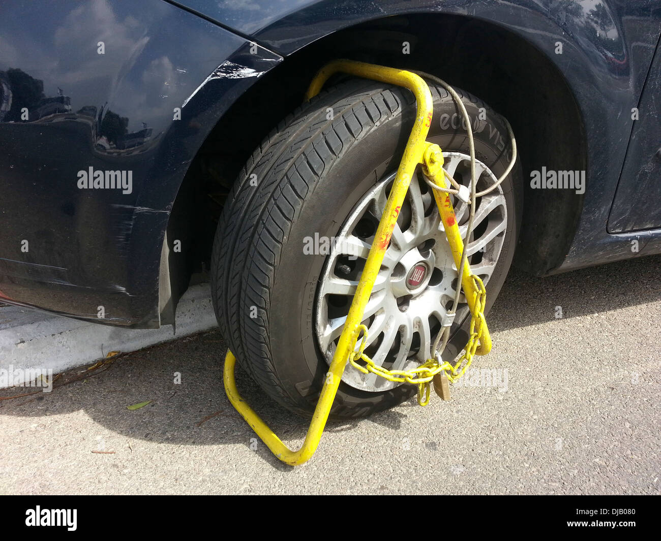 Car wheel clamped for illegal parking - Stock Image