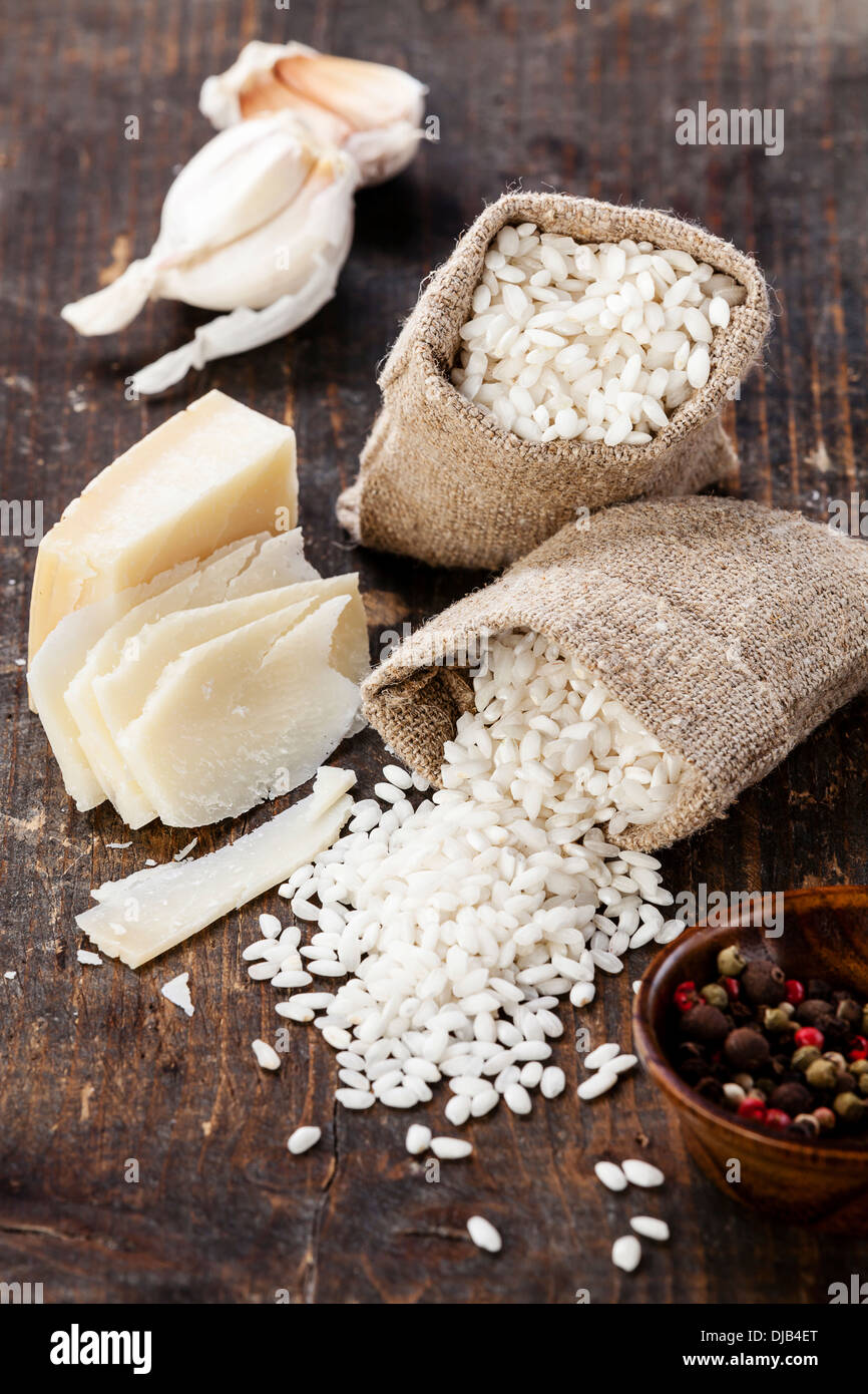 Raw white rice in burlap bag with ingredients for risotto - Stock Image