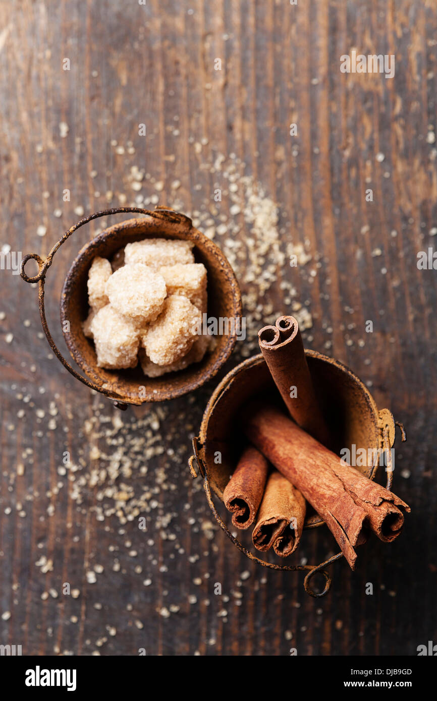 Cinnamon sticks and brown sugar on wooden background - Stock Image