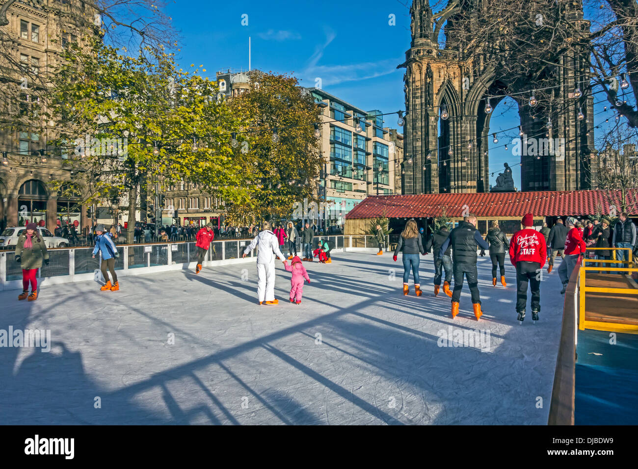 Edinburgh's Christmas in East Princes Street Gardens with ice rink and skaters with Scott Monument behind Stock Photo