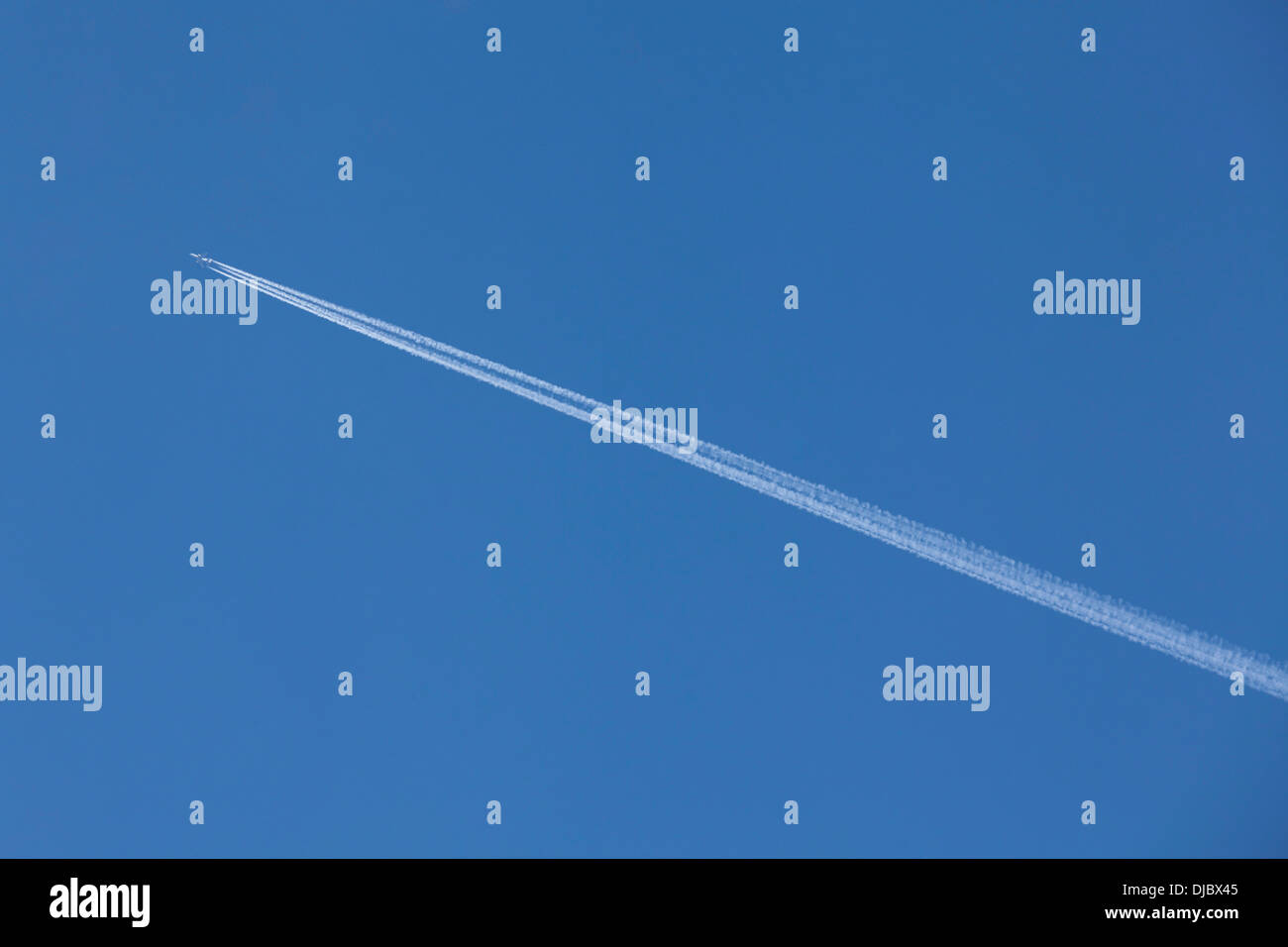 Flying airoplane on the blue sky leaving white lines behind - Stock Image
