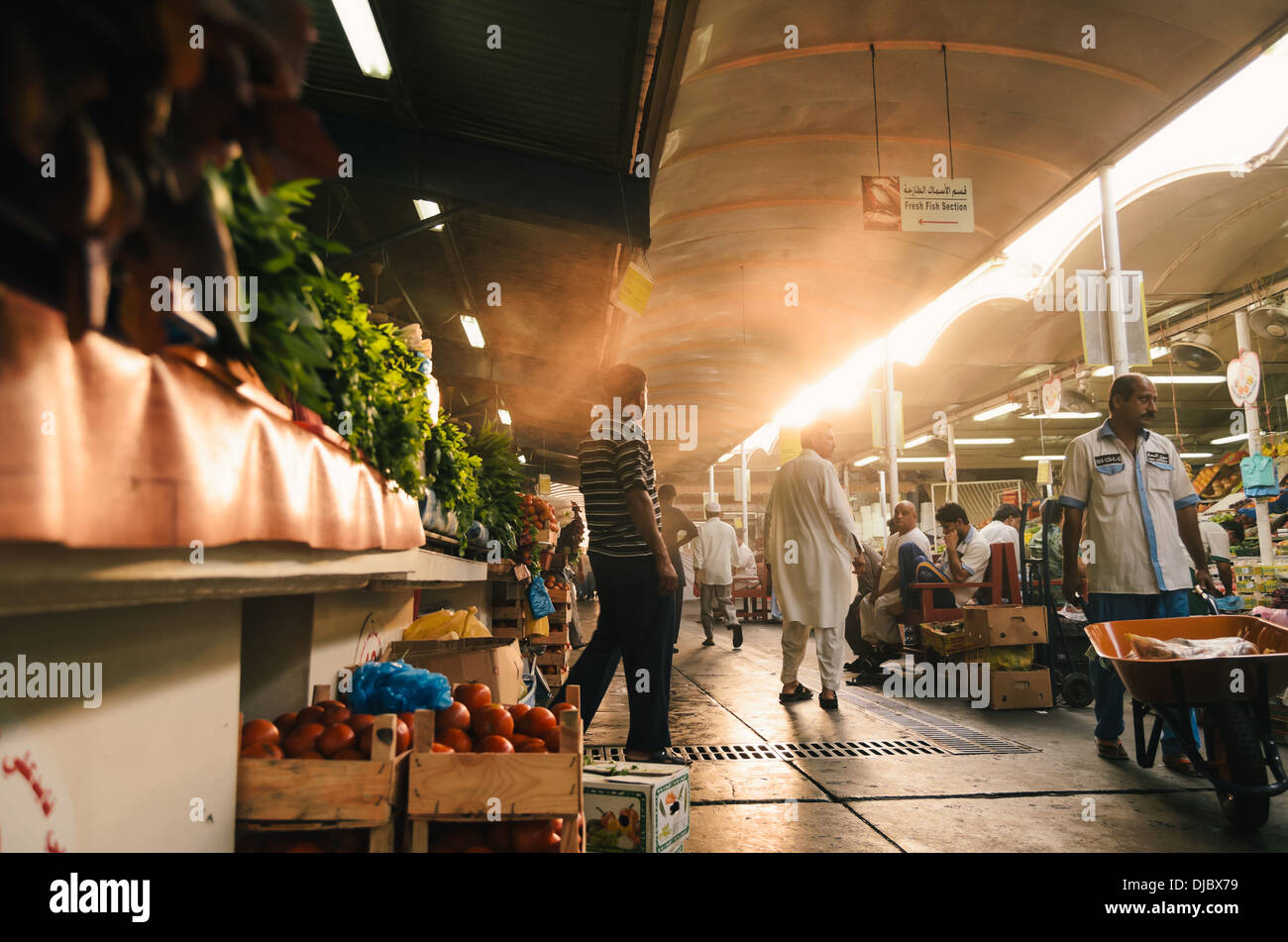 Arab men walking along one of the corridors at Deira's Fruit and Vegetable Market during sunrise. Dubai, UAE. - Stock Image