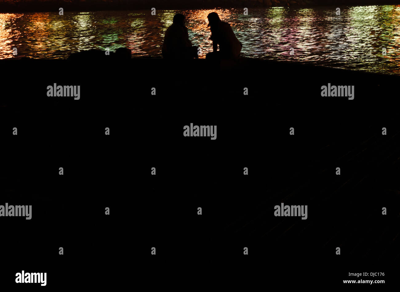 Two men sitting by the Dubai Creek are silhouetted against the water as it glitters with colorful lights of nearby Stock Photo