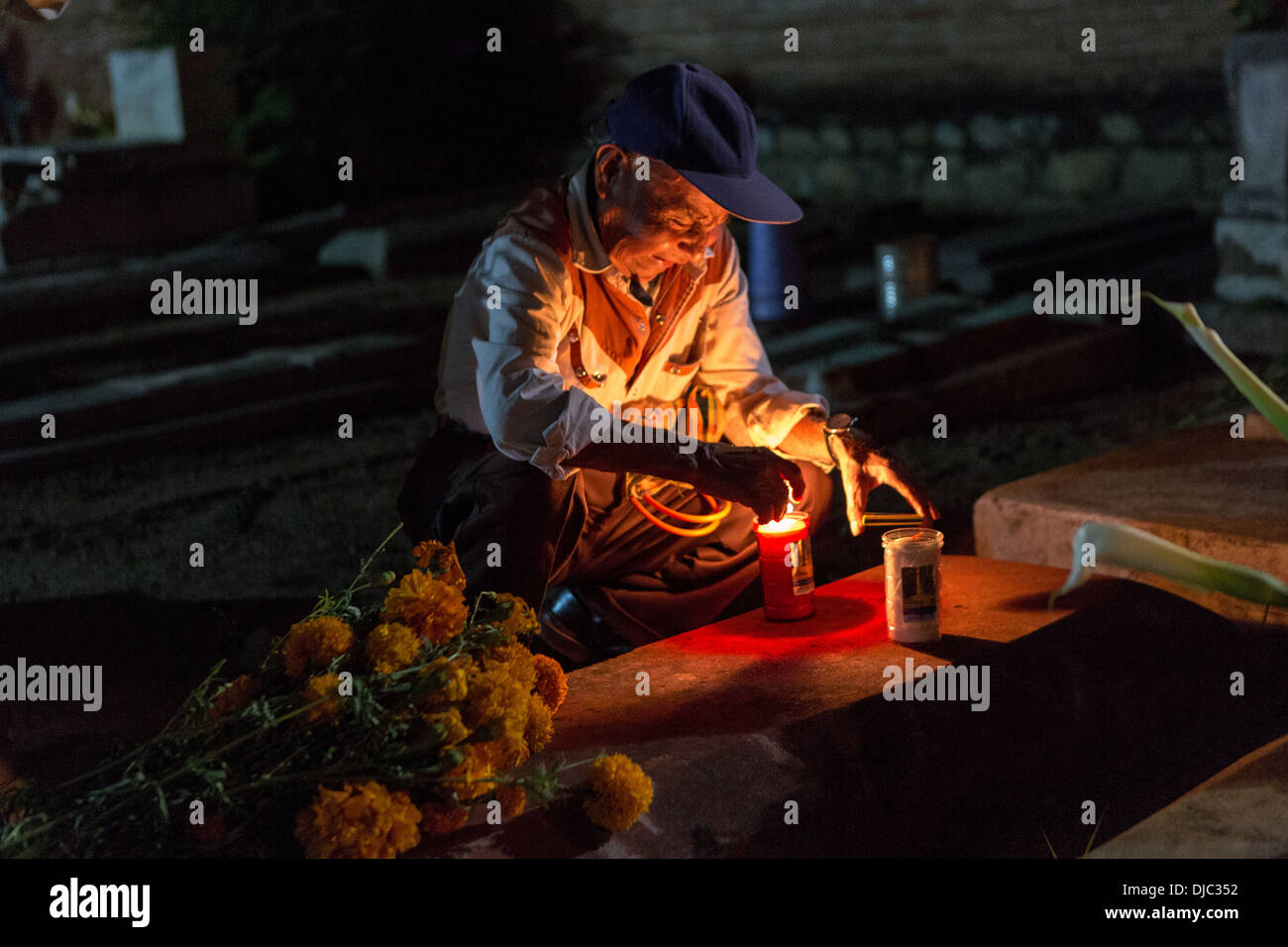 An elderly Mexican cries as he lights a candle at the gravesite of his wife for Day of the Dead festival known in spanish as Día de Muertos at the old cemetery October 31, 2013 in Xoxocotlan, Mexico. - Stock Image