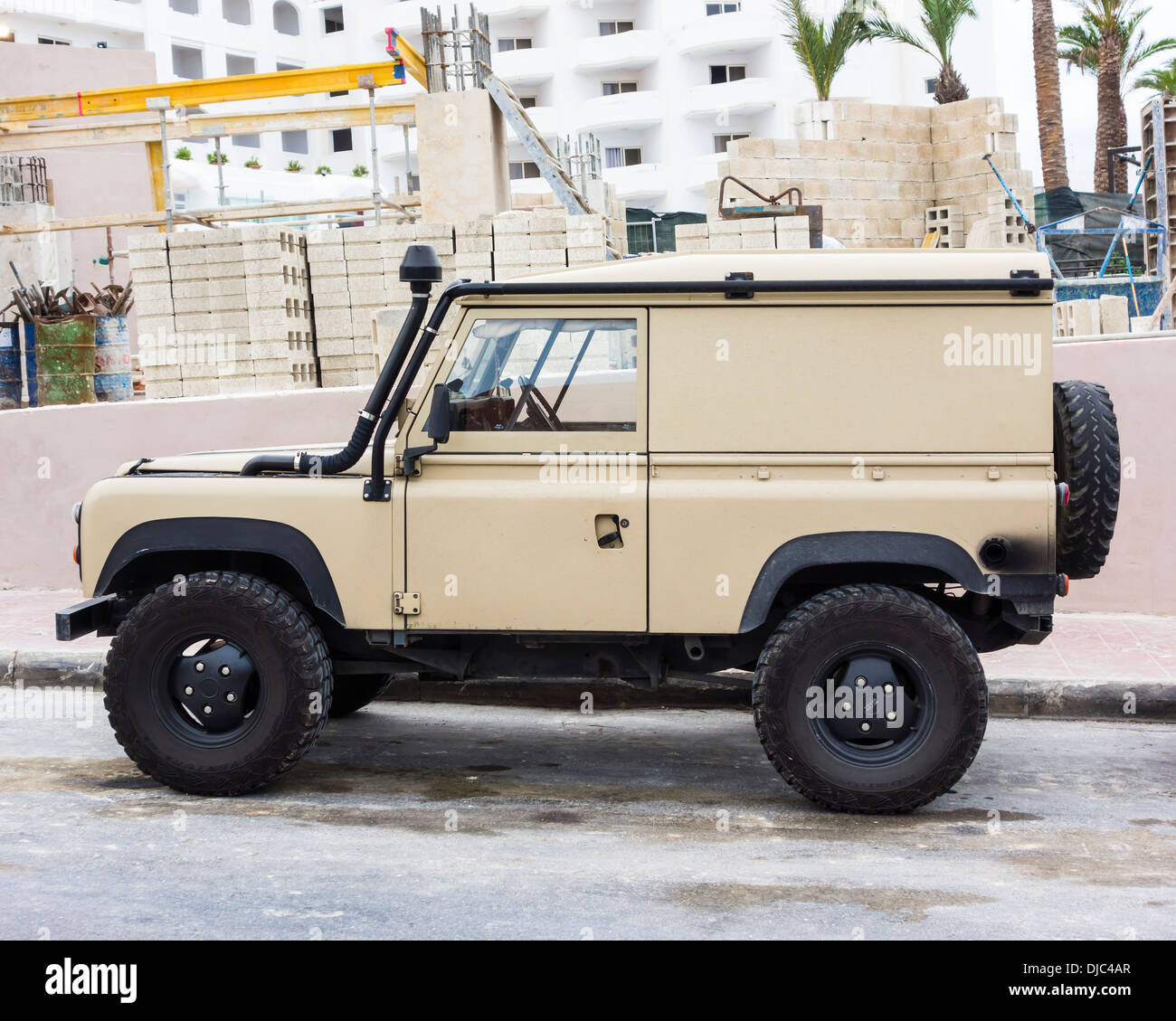 Commercial Land Rover Defender hardtop parked next to a construction site Europe . - Stock Image