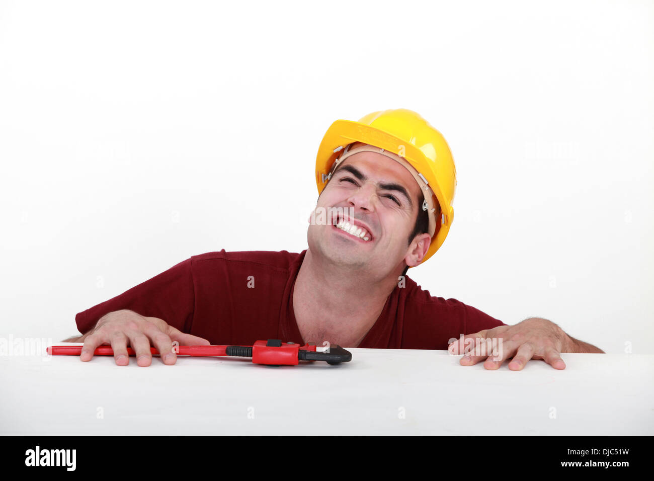Grunting tradesman trying to lift himself up onto a ledge - Stock Image
