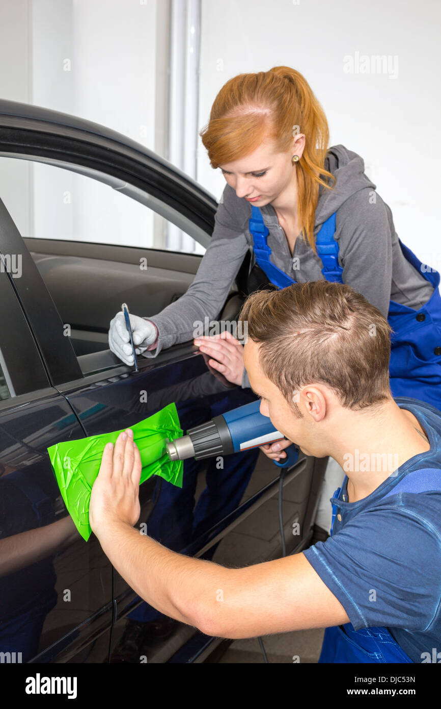 car wrapping professional wrapping car door handle in colorful foil or film using a squeegee Stock Photo
