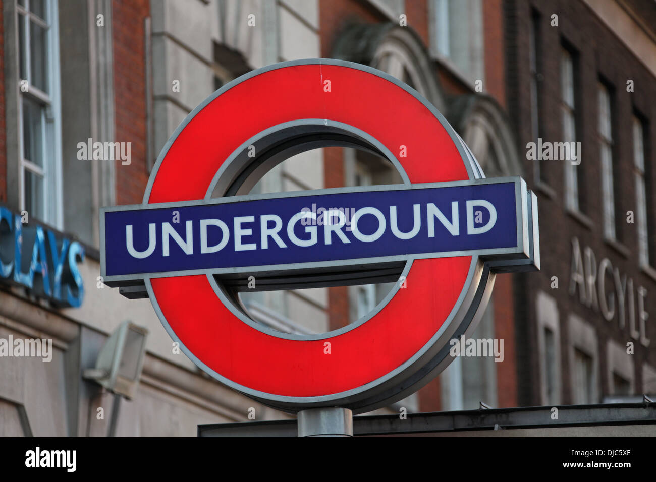 A close up picture of a 'London underground' sign near Kings Cross, positioned next to a subway that leads to the underground. - Stock Image