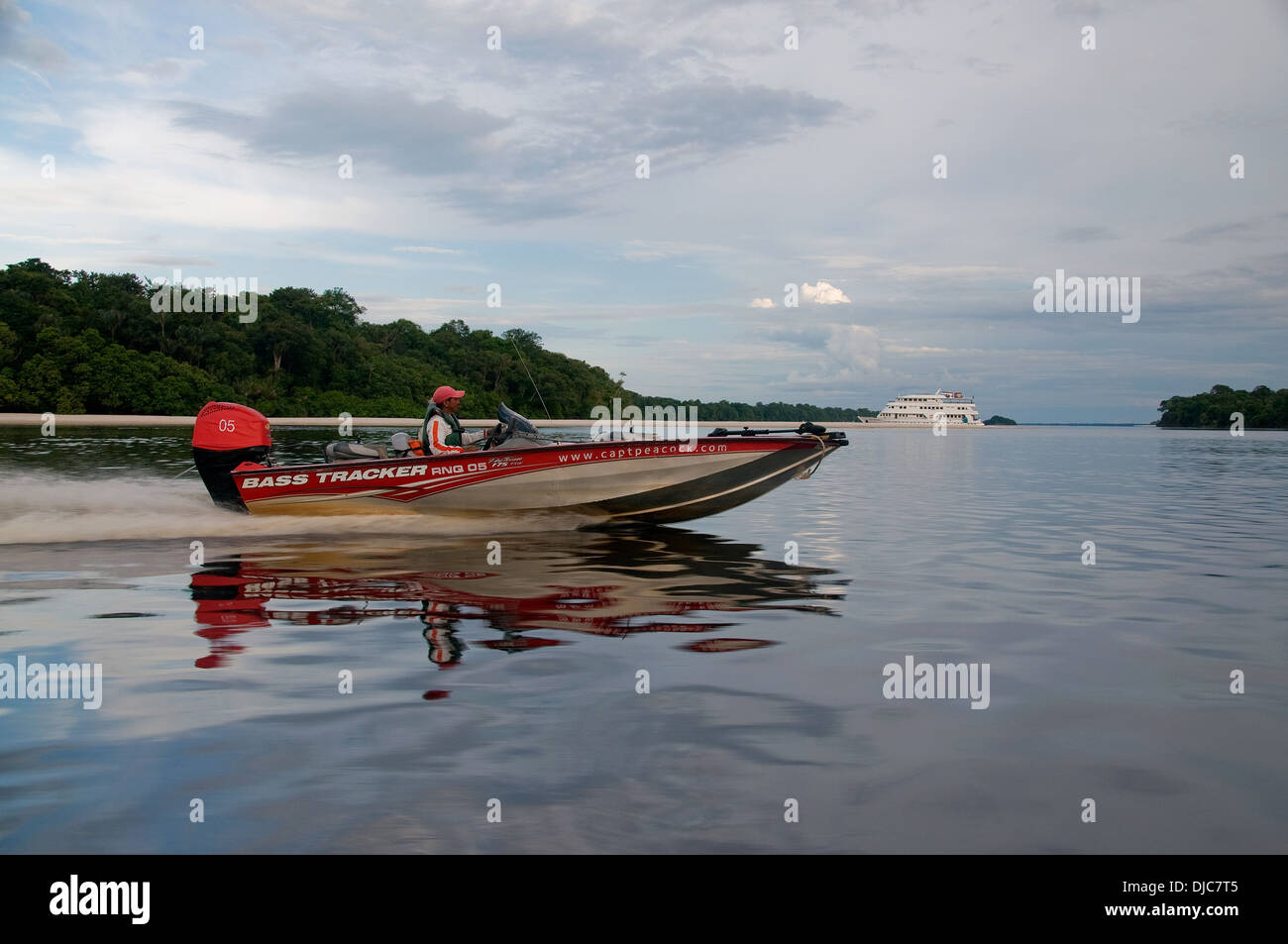 A bass boat heads for a luxury fishing and ecotour yacht anchored in a tributary in Brazil's Amazon River Basin. - Stock Image